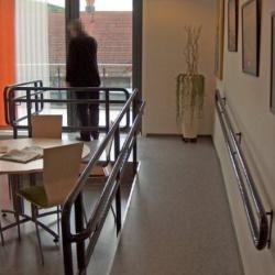 Ramp with railing on eaither side leading up to a wide glass door that opens to the outdoors