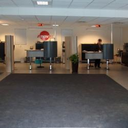the front reception area with a dark grey rug providing a color contrast and leading visitors toward the backlit reception area with the red NAV logo visible from the entry.