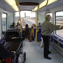 Interior of metro car with passengers as it travels above ground.