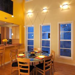 Three parallel windows that begin low to the floor in dining area